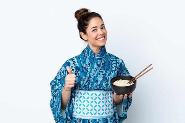 Mulher vestindo quimono sobre parede branca isolada com polegares para cima, porque algo de bom aconteceu enquanto segura uma tigela de macarrão com pauzinhos