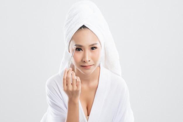 Mulher vestindo roupão de banho com toalha na cabeça está usando um pincel de maquiagem, maquiagem após o banho isolado no branco.