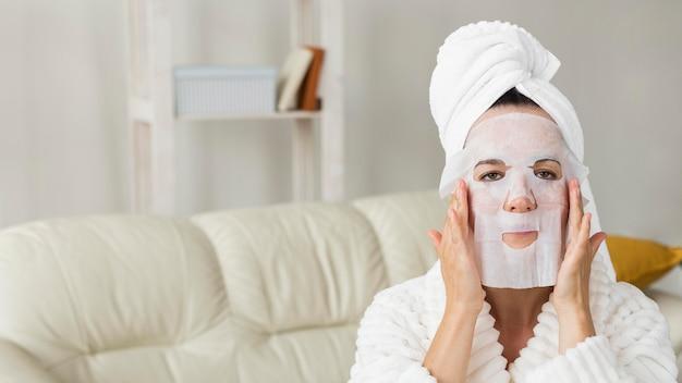 Mulher vestindo roupão de banho e aplicando máscara facial