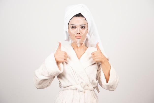 Mulher vestindo roupão de banho e toalha com máscara.