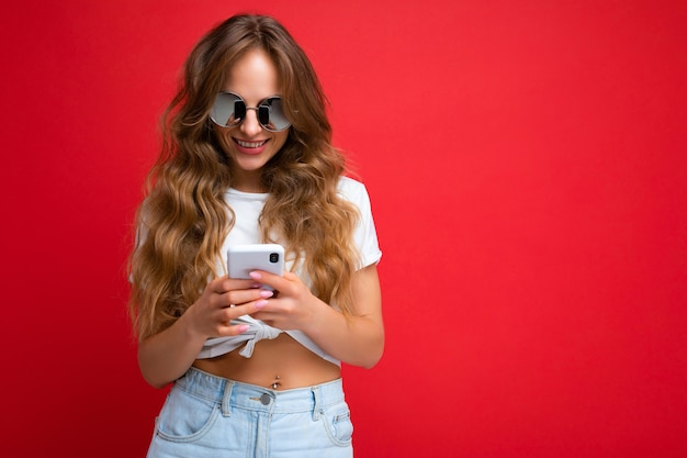 Mulher vestindo roupas casuais em pé isolado sobre o fundo navegando na internet através do telefone, olhando para a tela do celular.