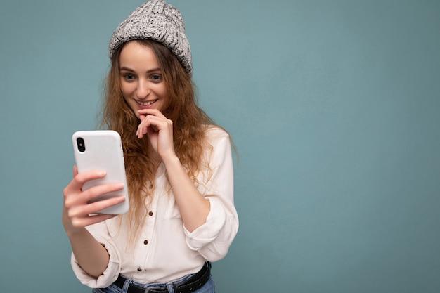 Mulher vestindo roupas casuais, isolada sobre o fundo, navegando na internet