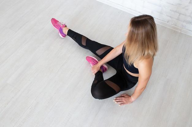 Mulher vestindo roupas de esporte, sentada no chão
