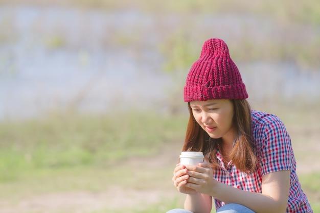 Mulher vestindo roupas de malha quente, beber chávena de chá quente ou café ao ar livre na luz solar
