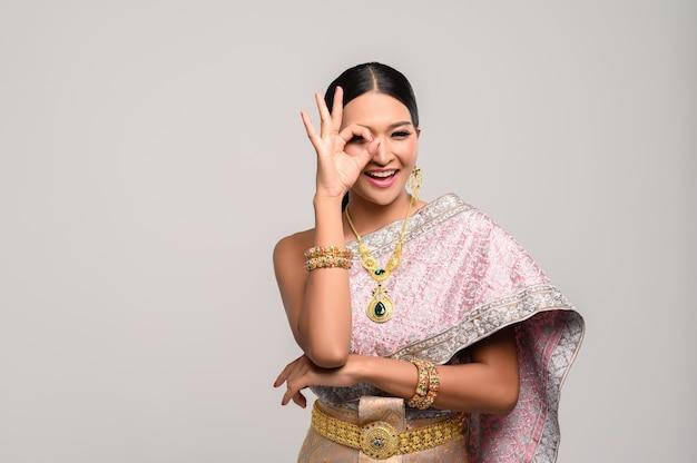 Mulher vestindo roupas tailandesas e mão simbolizando ok