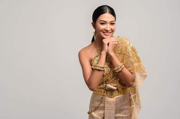 Mulher vestindo roupas tailandesas e mãos tocando o queixo