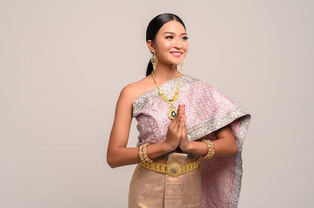 Mulher vestindo roupas tailandesas que pagam respeito