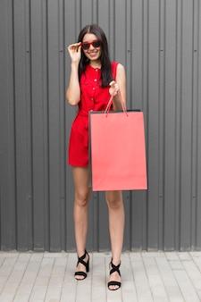 Mulher vestindo roupas vermelhas e segurando sacolas com vista frontal