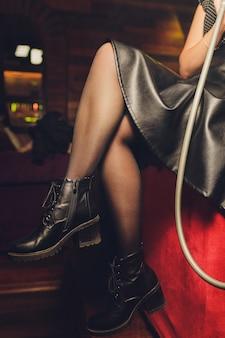 Mulher vestindo saia e botas em uma barra de shisha
