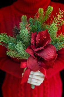Mulher vestindo suéter vermelho segurando buquê de flores de natal