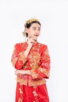 Mulher vestindo terno cheongsam está fazendo uma sessão de fotos para promover as compras de viajantes do evento no ano novo chinês
