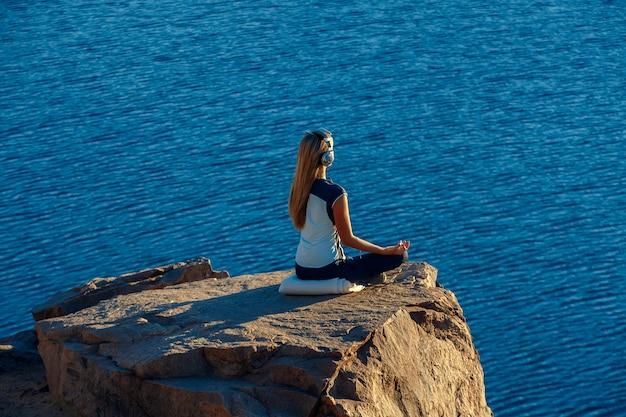 Mulher vestindo terno esporte e fones de ouvido, sentado em posição de lótus na rocha acima do mar, meditando, ouve música. yoga ao ar livre.