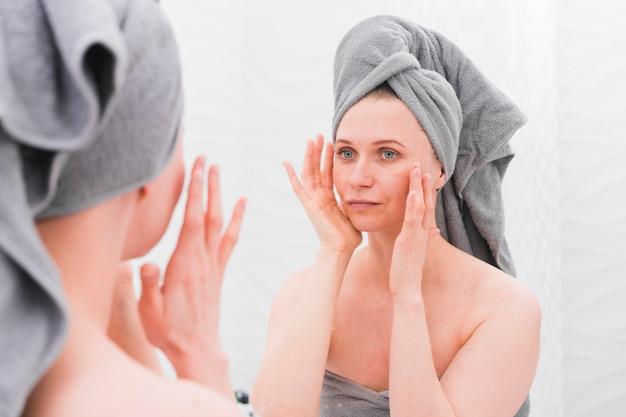 Mulher vestindo toalhas e olhando no espelho