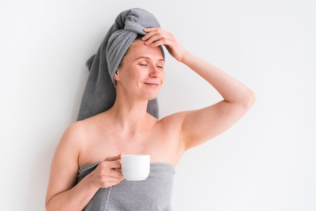 Mulher vestindo toalhas e segurando uma xícara