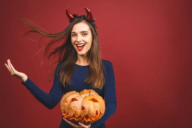 Mulher vestindo traje de diabo preto halloween com bandana da bruxa para uma festa temática. ela segura a abóbora por um 'truque ou travessura'