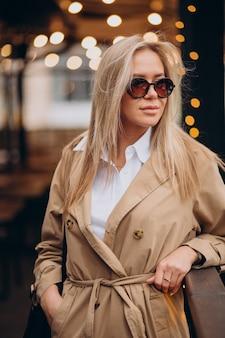 Mulher vestindo um casaco bege e andando na rua no natal