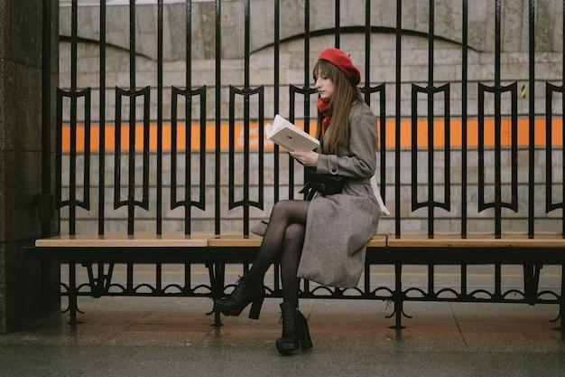 Mulher vestindo um casaco, boina e lenço sentada sozinha na estação de metrô de são petersburgo lendo um livro