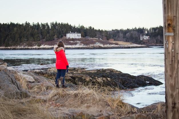 Mulher vestindo um casaco vermelho em pé na praia com a superfície da grama seca