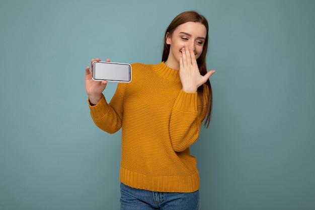 Mulher vestindo um suéter laranja poising isolado na parede azul com um espaço vazio segurando na mão e mostrando o celular com um espaço vazio