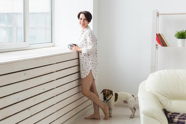 Mulher vestindo uma camisa aconchegante relaxando em casa e brincando com o cachorro jack russell terrier, bebendo
