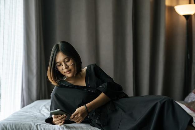 Mulher vestindo uma camisa preta, deitada na cama e jogando smartphone.