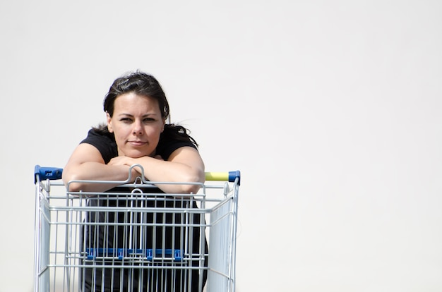 Mulher vestindo uma camisa preta encostada em um carrinho de compras com um fundo branco