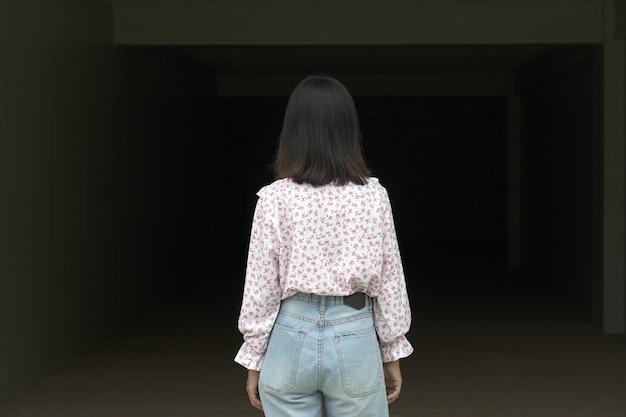 Mulher vestindo uma camisa rosa encontrou um caminho escuro.