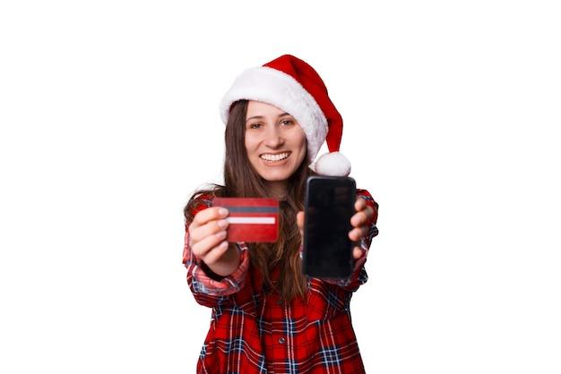 Mulher vestindo uma camisa xadrez está mostrando para a câmera o cartão que ela tem e a tela do telefone.