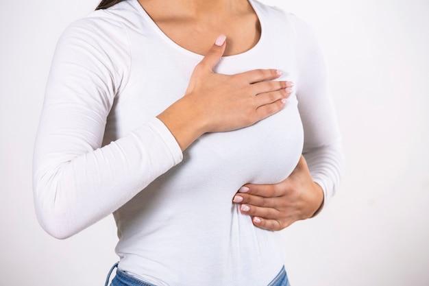 Mulher vestindo uma camiseta branca, verificando a mama, autoexame das mamas (bse)