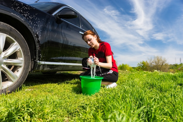 Mulher vestindo uma camiseta vermelha lavando um veículo preto no campo, agachada ao lado de um balde verde torcendo a esponja com sabão em um dia ensolarado