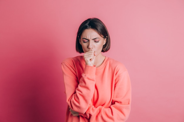 Mulher vestindo uma camisola casual no fundo, sentindo-se mal e tossindo como sintoma de resfriado ou bronquite. conceito de saúde.