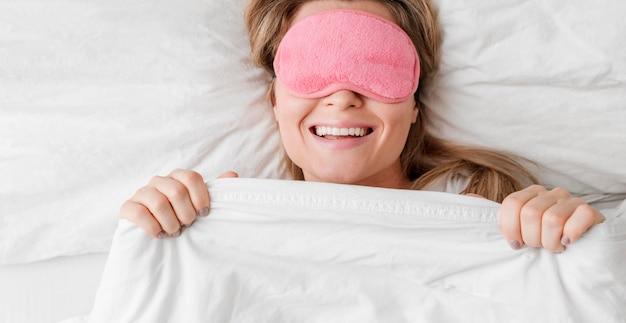 Mulher vestindo uma máscara de dormir sobre os olhos e sorrisos