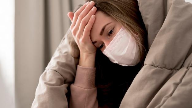 Mulher vestindo uma máscara médica dentro de casa