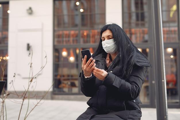 Mulher vestindo uma máscara protetora, sentado na rua, usando telefone celular