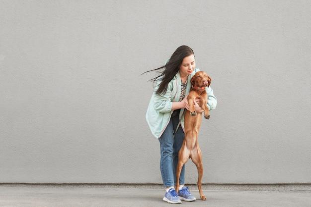 Mulher vestindo uma roupa casual vestindo um cachorro em pé