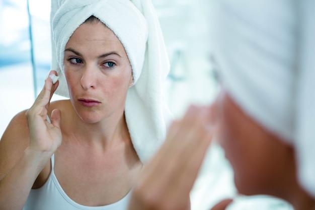 Mulher vestindo uma toalha no cabelo está aplicando creme para o rosto no espelho