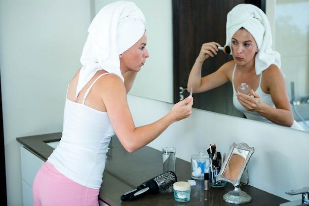 Mulher vestindo uma toalha no cabelo está aplicando pó facial no espelho