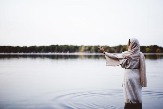 Mulher vestindo uma túnica bíblica e de pé na água com a mão para cima