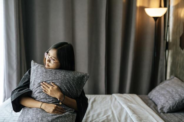 Mulher vestindo uma túnica preta, abraçando o travesseiro na cama.