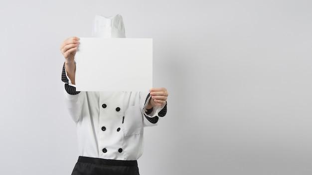 Mulher vestindo uniforme de chef e segurando papel a4 em branco sobre fundo branco.