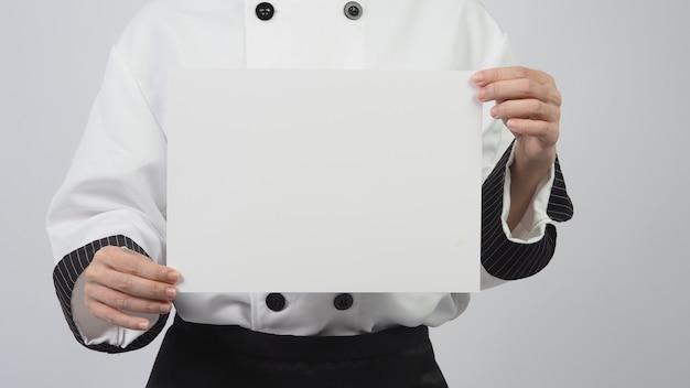 Mulher vestindo uniforme de chef e segurando papel a4 em fundo branco.