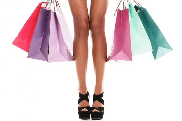 Mulher vestindo várias sacolas coloridas