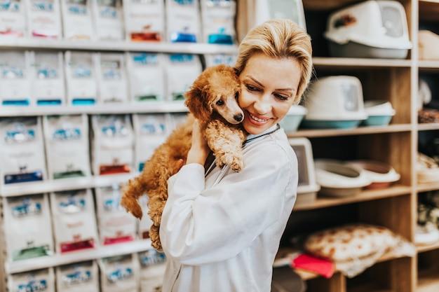 Mulher veterinária de meia-idade feliz e sorridente em pé na loja de animais e segurando um lindo poodle vermelho em miniatura.