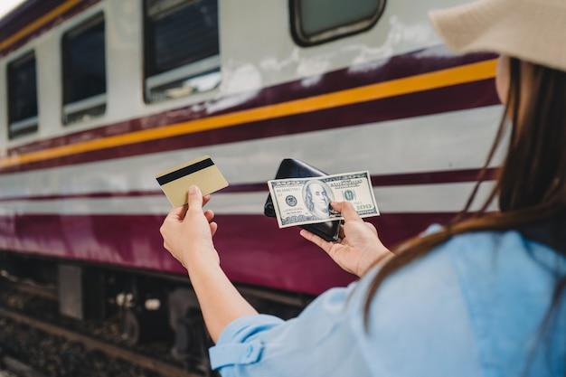 Mulher, viagem de trem, menina, com, mochila, mostrar, dela, mãos, com, cartão crédito, e, dólares americanos