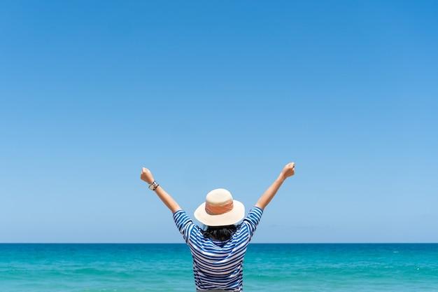 Mulher viaja ao redor do mundo com liberdade de verão na praia e vida relaxante