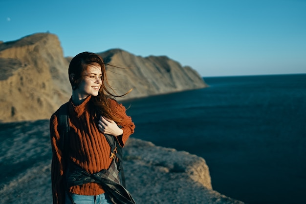 Mulher viaja na natureza, nas montanhas com uma mochila perto do mar