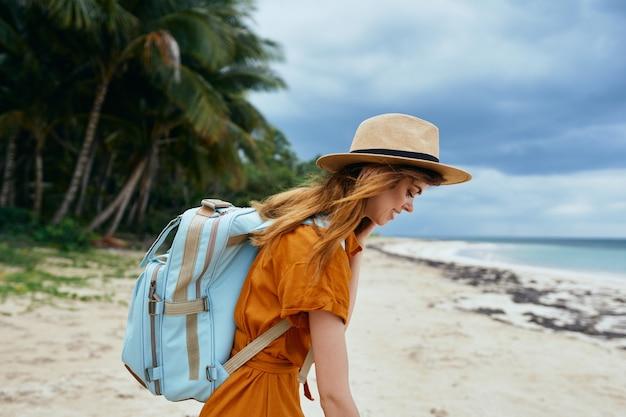 Mulher viaja na praia perto do mar com uma mochila nas costas e árvores altas ao fundo