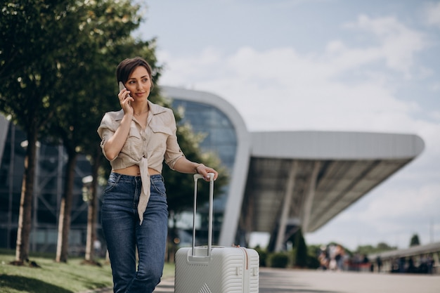 Mulher viajando com bagagem no aeroporto e falando ao telefone
