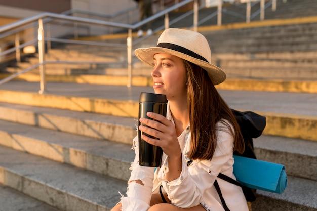 Mulher viajando com chapéu e mochila segurando uma garrafa térmica