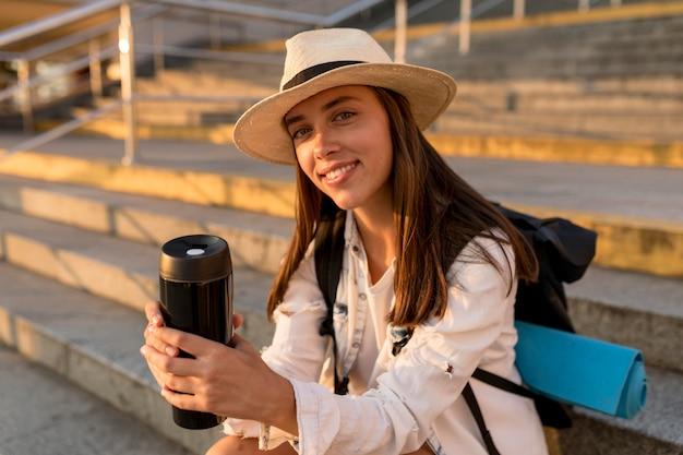 Mulher viajando com mochila e chapéu segurando uma garrafa térmica